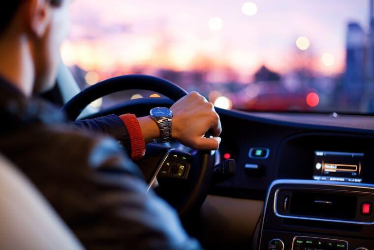 男性が運転中にaudibleオーディブルを聴いてドライブしている所